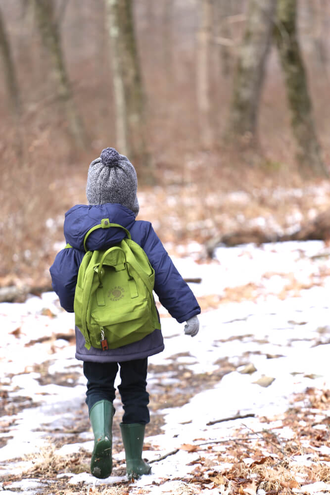 Boy hiking in blue coat green backpack in snow