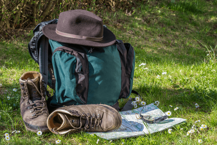 Backpack, Boots, Hat, and Map in grass